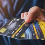 複数のクレジットカードを差し出す人